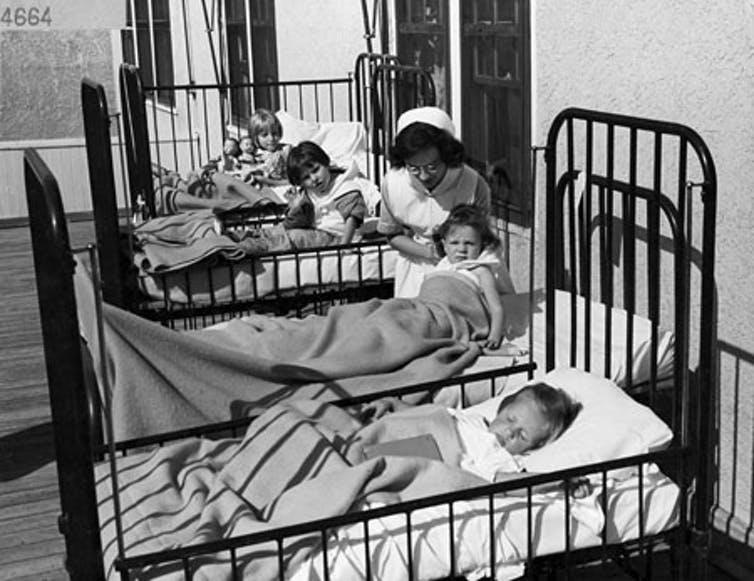 Photo noir et blanc d'enfants dans une rangée de lits d'hôpital avec une infirmière