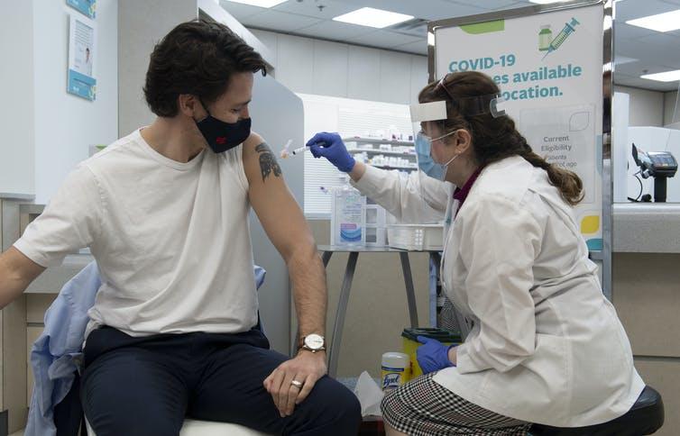 Le premier ministre du Canada, Justin Trudeau, la manche de son t-shirt blanc relevée, est vacciné par une femme en sarrau blanc