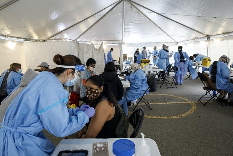 Les personnes masquées sont vaccinées par des agents de santé en tenue de protection sous une tente