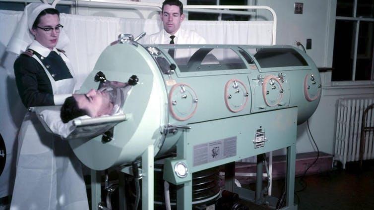 Une infirmière se tient debout près d'un homme dans un poumon d'acier