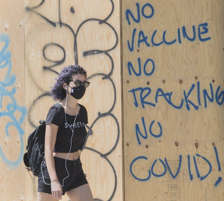 Une femme porte un masque de protection alors qu'elle passe devant un graffiti anti-vaccins