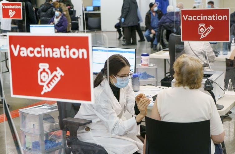 une femme administre un vaccin à une autre femme, assise, de dos